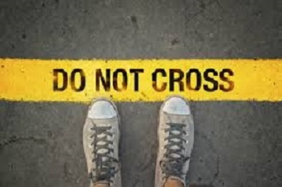 Image of two feet standing behind the yellow line that reads